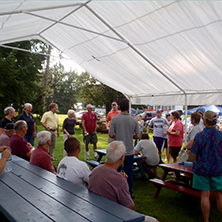 Community gathering under a tent, summertime