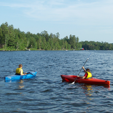 Two kayakers on a lake with pine trees on shore beyond.